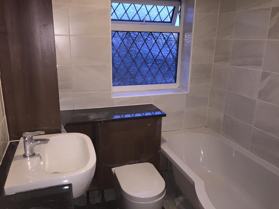 bathroom refit with grey tiles and dark wood boxing