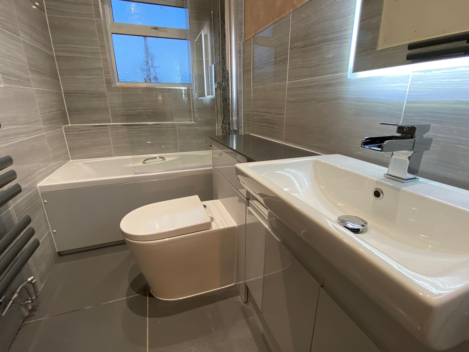bathroom refit with grey tiles and white suite
