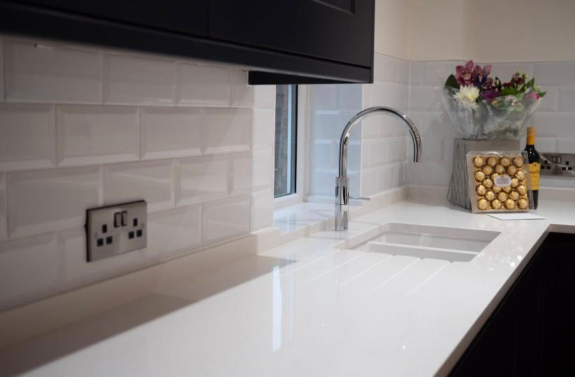 Glossy white worktop and tiles with set sink